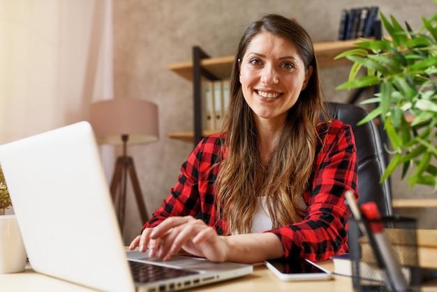 Женщина занимается серфингом в интернете со своим ноутбуком. она работает дома как умная работа