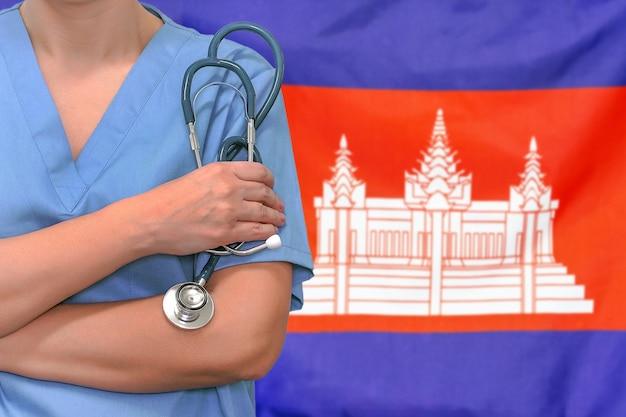 Женщина-хирург или врач со стетоскопом против флага камбоджи