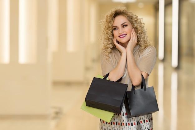 여자 놀람 손으로 뺨을 보유 하고있다. 왼쪽 찾고 가리키는 쇼핑 가방과 함께 아름 다운 소녀. 당신의 제품을 소개합니다. 표정 표정