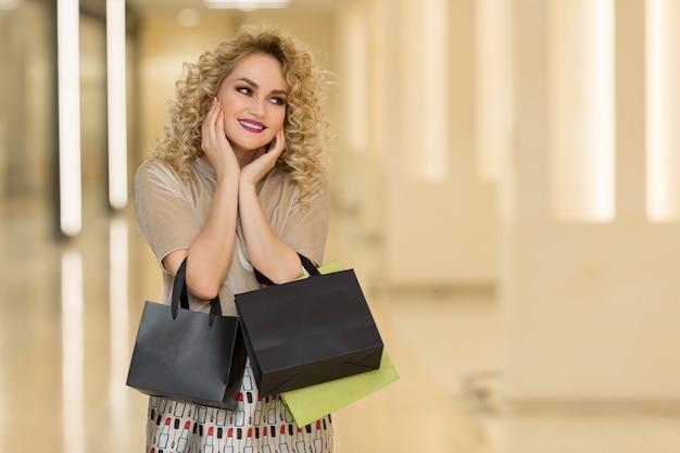 여자 놀람 손으로 뺨을 보유 하고있다. 오른쪽 찾고 가리키는 쇼핑 가방과 함께 아름 다운 소녀. 당신의 제품을 소개합니다.