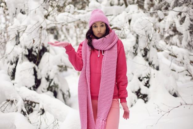 ピンクの服を着た女性の驚きジャケット、ニットのスカーフ、帽子は冬の雪の森に立っています