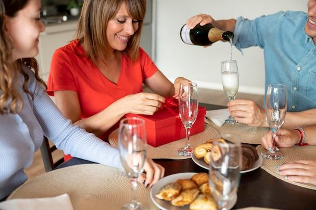 Женщина удивлена подарком на семейном празднике