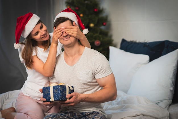 Woman surprising man with gift in bedroom
