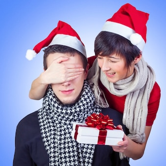 Woman surprising man with gift for new year