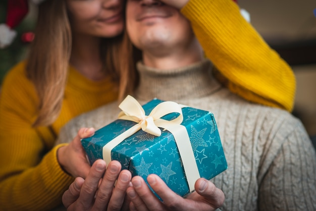 Woman surprising man with gifts