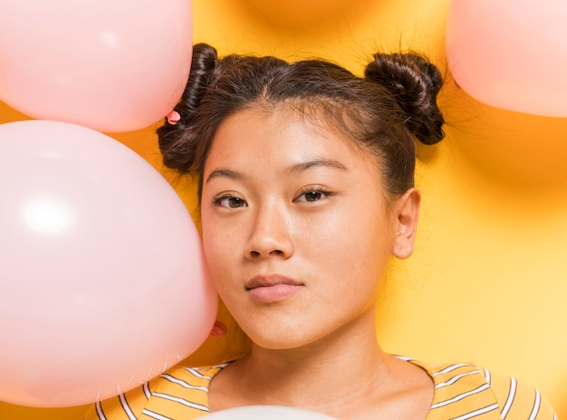 Woman surrounded by balloons looking at camera