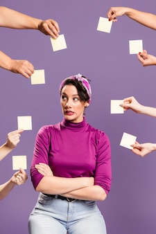 Woman surrounded by hands and sticky notes being anxious