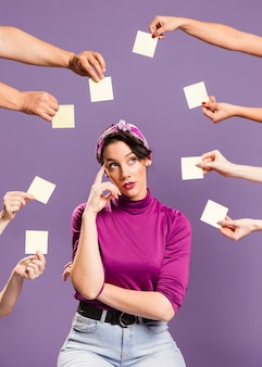 Woman surrounded by hands and sticky notes being bored