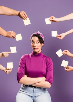 Woman surrounded by hands and sticky notes being indifferent