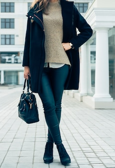 Woman in a sweater, black coat and pants holding a handbags while walking in the city