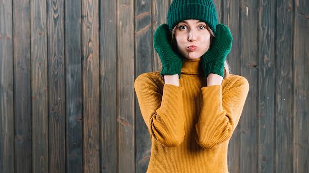 Woman in sweater blowing cheeks