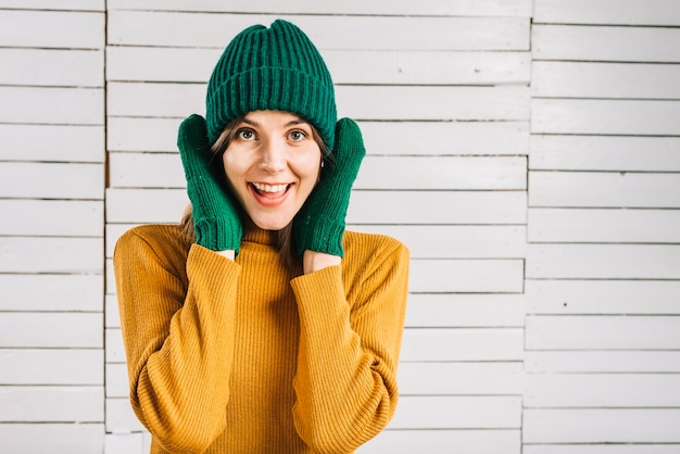 Woman in sweater covering ears