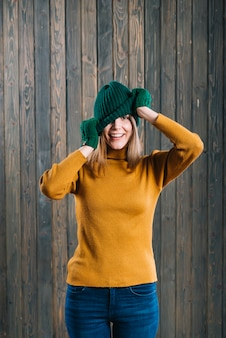 Woman in sweater covering face with cap