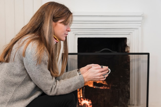 Woman in sweater drinking tea near fireplace
