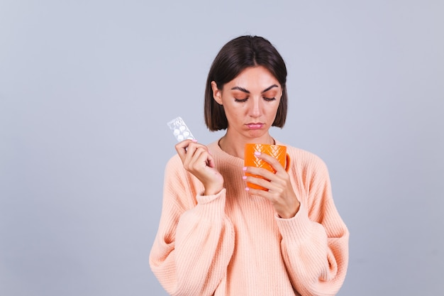 Woman in sweater on gray wall holds mug and pills with unhappy sad expression on face