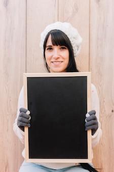 Woman in sweater holding chalkboard