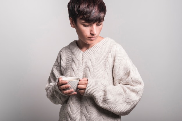 Woman in sweater holding coffee cup standing against gray background