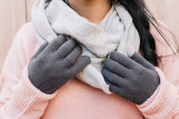 Woman in sweater holding hands on scarf