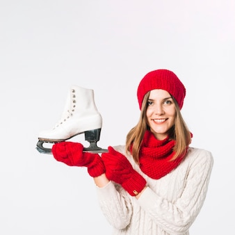 Woman in sweater holding skate