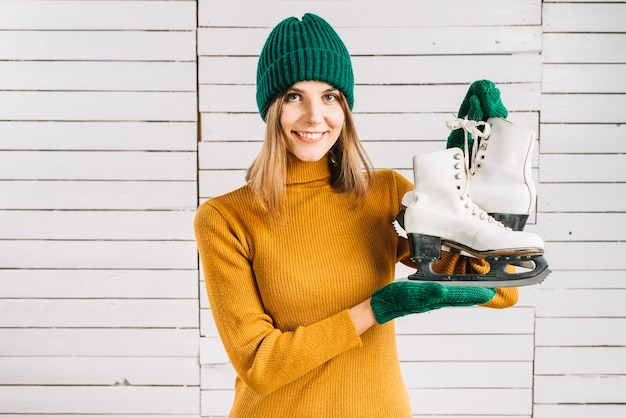 Woman in sweater holding skates