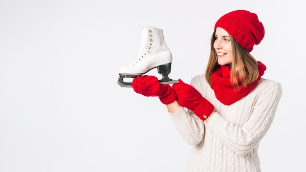Woman in sweater holding white skate