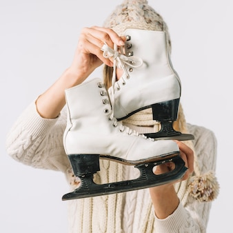 Woman in sweater holding white skates