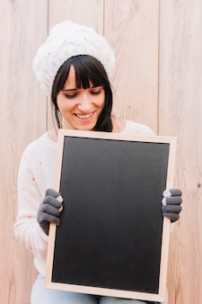 Woman in sweater looking at chalkboard