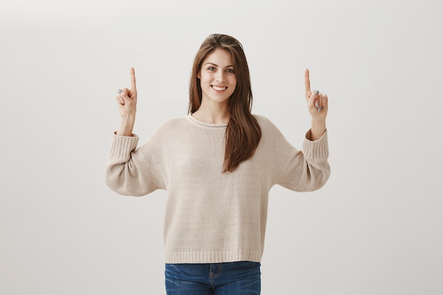 Woman in sweater pointing fingers up at copyspace