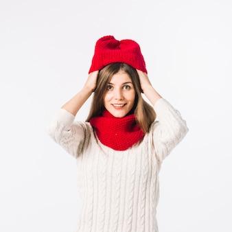 Donna in maglione mettendo il cappello