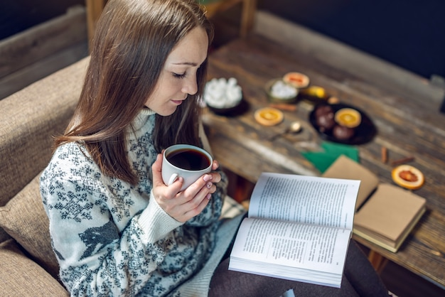 Woman in a sweater reading a book with a mug of coffee in the evening in a warm christmas atmosphere. cozy new year mood