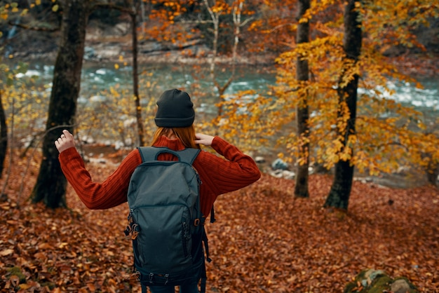 Woman in a sweater with a backpack and in jeans walks through the autumn forest in the mountains