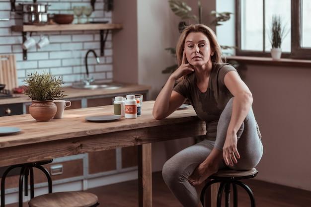 汗をかく女性。離婚後、気分が悪くてストレスを感じながら汗をかく金髪の熟女