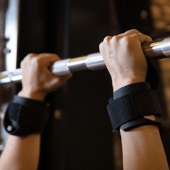 Потные руки женщины, выполнять упражнение на турнике в тренажерном зале