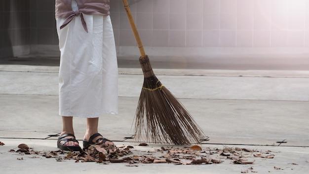 Женщина подметает сухие листья на цементном полу длинной деревянной метлой и поддерживает чистоту на улице