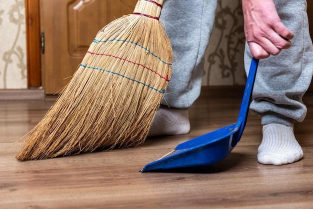 ほうきを使って床を掃除する女性