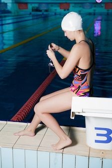 水泳帽をかぶった女性スイマーは眼鏡をかけ、泳ぐ準備ができています