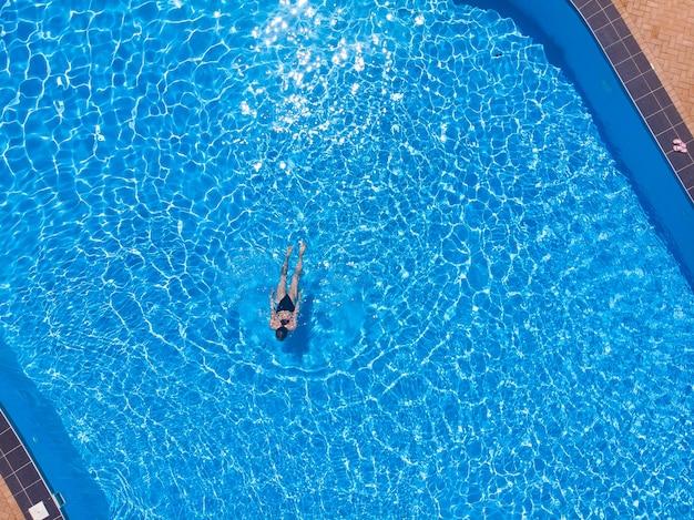 Женщина плавает в бассейне сверху, вид сверху с дрона, летний отдых в отеле