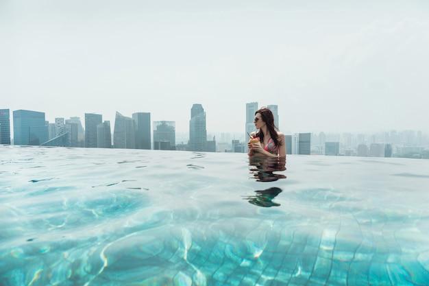 Женщина плавает в открытом бассейне на крыше в сингапуре. молодая женщина с кокосом в руках расслабляется в открытом бассейне на крыше