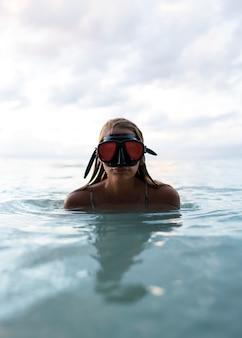 スキューバダイビング機器で海で泳ぐ女性
