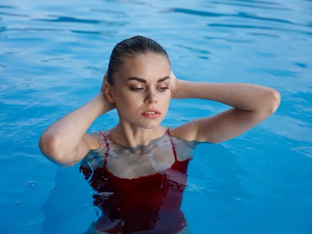 水着休暇の自然の中でプールで泳ぐ女性
