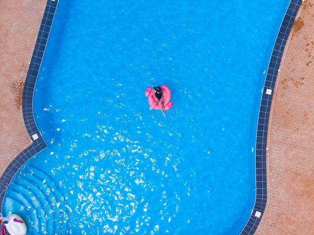 플라밍고 수영장에서 수영하는 여성은 크고 고급스러운 수영장에 떠 있고 드론 공중 전망