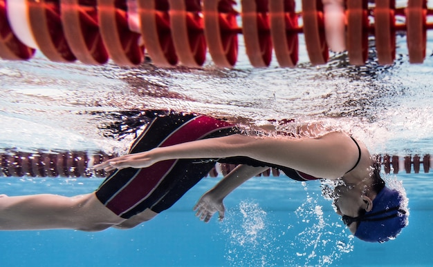Woman swimming pool she turning back .underwater photo