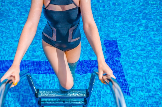 Woman swimming in the pool. woman with swimsuit swimming on a blue water pool.
