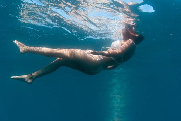 海の下で泳ぐ女性
