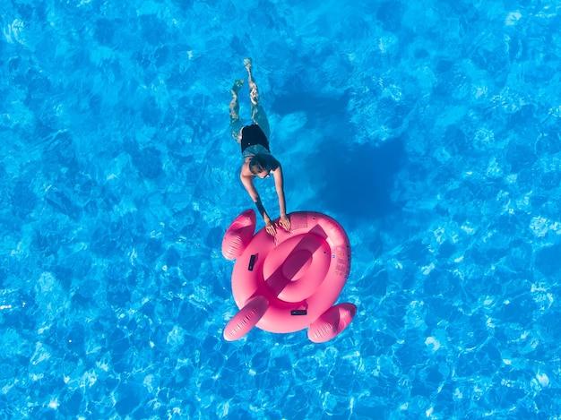 분홍색 플라니고 풀로 수영하는 여성은 위에서 본 수영장, 드론의 공중 꼭대기 전망, 호텔에서의 여름 휴식