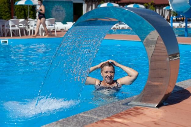 金髪のプールの青い水で泳ぐ女性は、トロピカルリゾートのアクアパークの滝で休んでいます...
