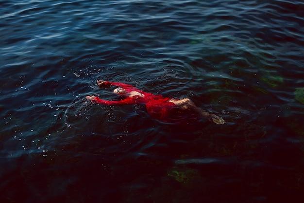 Женщина плавает в море в красном длинном платье с солнцезащитными очками летом