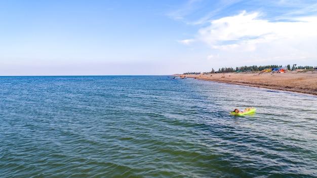 Женщина плывет по морю на матрасе, глядя на море