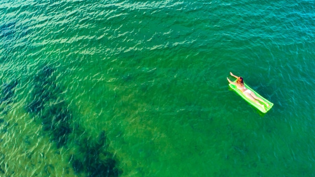 Woman swims on the sea on a mattress looking at the sea