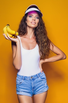 Woman in swimsuit and blue shorts holding banana and posing isolated over yellow scene